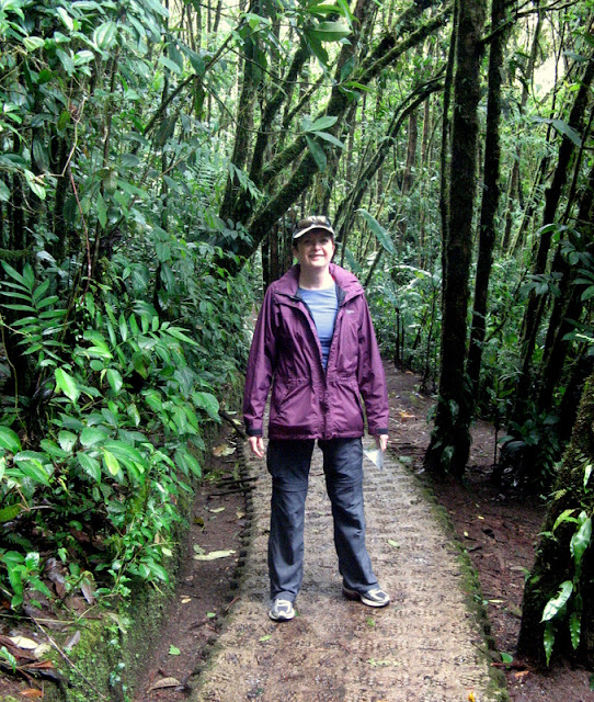 woman in wet pants and jacket on a trail through the rainforest, Costa Rica