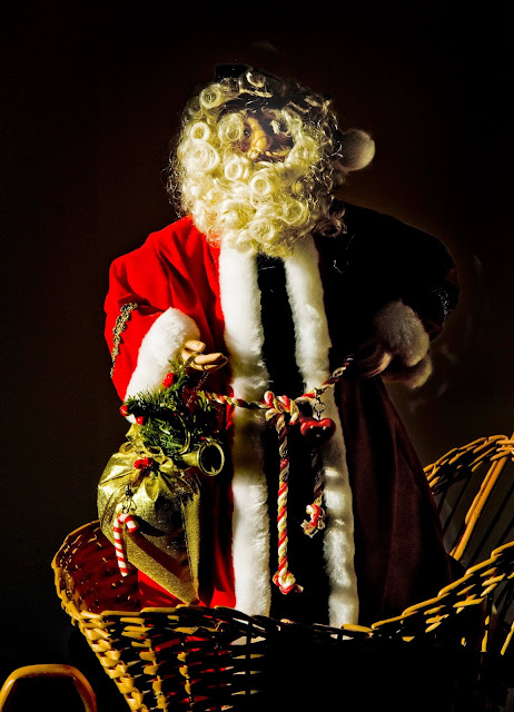 A porcelain Santa Clause dressed in velveteen clothing standing in a wicker sleigh.