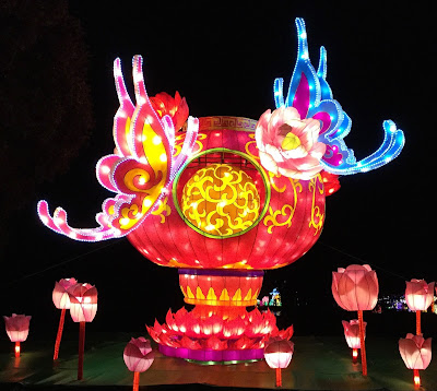 Pic of larger than life lantern with butterfly and peony decorations against night sky in pink, red and blue