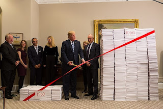 "Photo shows President Trump, surrounded by aides and holding a pair of scissors, about to cut red ribbon in front of two piles of papers: a small pile labeled ""1960"" and a large pile labeled ""today."""