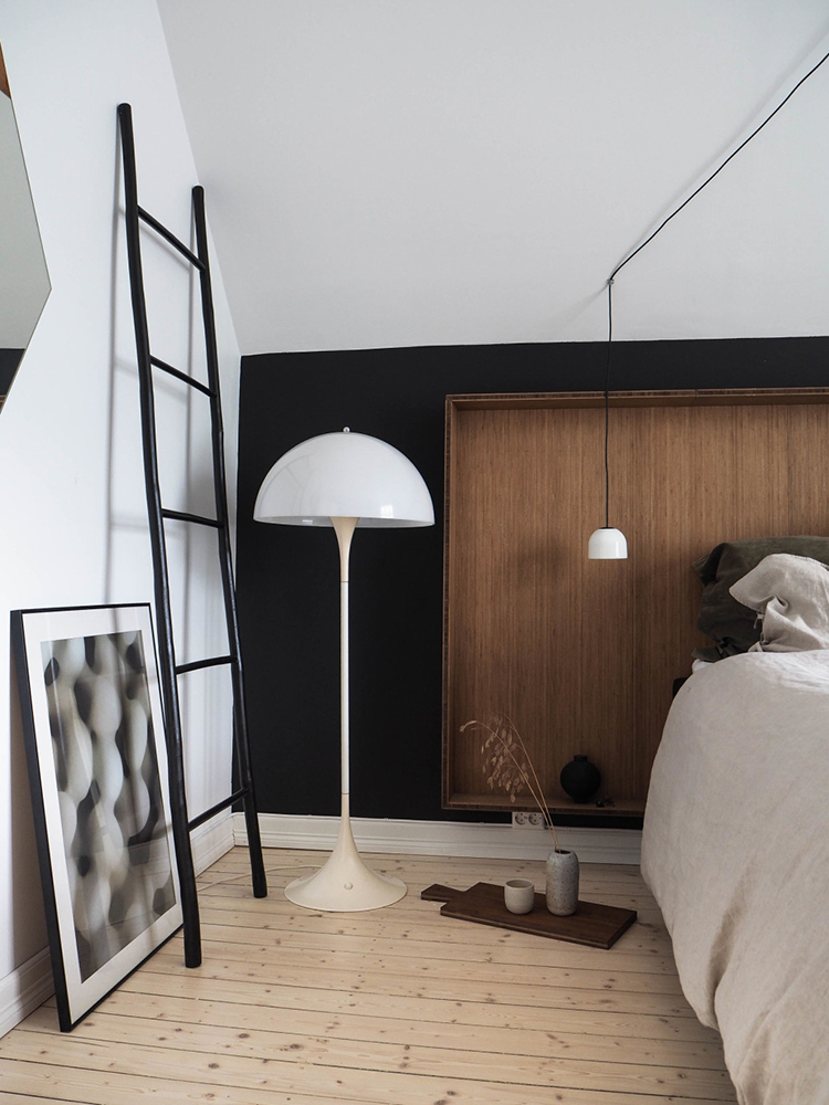 Scandinavian bedroom with black wall and wooden headboard via Only Deco Love