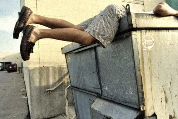 guy dumpster diving, but you can only see his legs sticking out of the dumpster