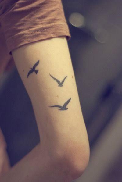 vemos el brazo de una mujer que lleva tatuaje de siluetas de gaviotas