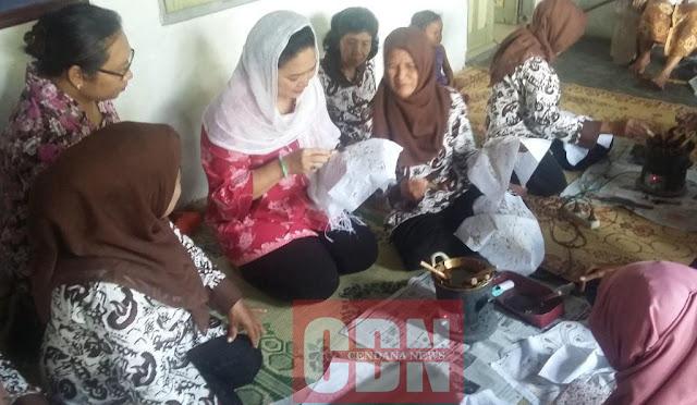 Titiek Soeharto sedang membatik menggunakan canting dalam bimbingan seorang pengrajin.