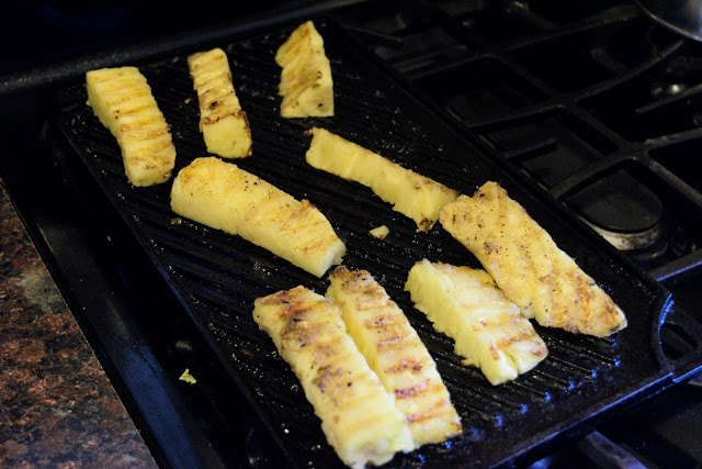 Pieces of pineapple cooking on the grill pan.
