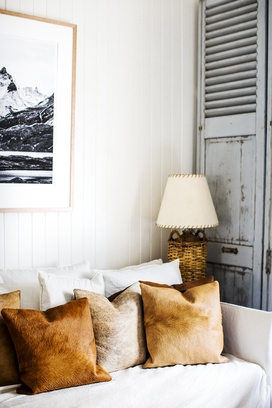 Rustic Bohemian Living Room Interior Design by Kara Rosenlund with white sofa and cowhide pillows. #rusticdecor #livingroom #texture #beachy #vintagestyle #interiordesign