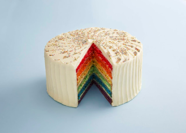 A cake covered in frosting and rainbow coloured hundreds and thousands, with a slice taken out to reveal 6 different coloured layers of sponge