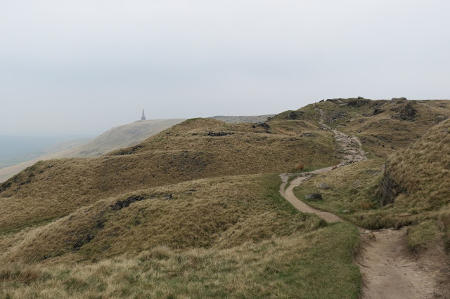 An undulating path weaves over and around the uneven hillside. To the left, the Stoodley Pike monument is just visible in the distance.