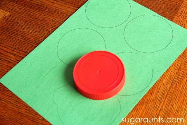 Trace a lid to make circles for cherry blossom tree craft.