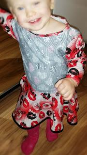Zdjęcie sukienki dla rocznej dziewczynki. Rozkloszowana w kolorze czerwono-szarym.