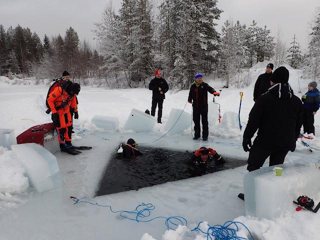 Kaksi sukeltajaa kolmionmallisessa avannossa, ympärillä jäällä muita ihmisiä ja kolmas sukeltaja