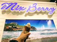 青い海のパネル前でソフトクリームを手にする