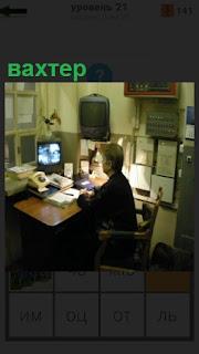 В помещении охраны сидит вахтер и ведет видео наблюдение за обьектом