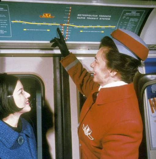 TTC guide Mrs. Verne Draper in uniform shows map of the new Crosstown route to Miss Gloria Sinibaldi