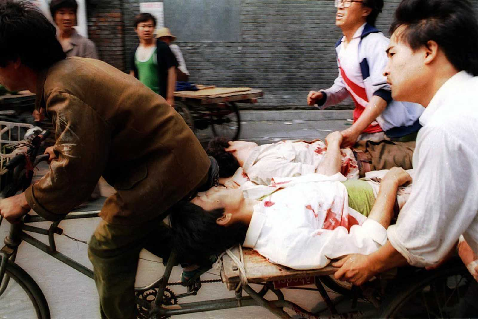 A rickshaw driver fiercely pedals wounded people to a nearby hospital, with the help of bystanders, on June 4, 1989. PLA soldiers again fired hundreds of rounds towards angry crowds gathered outside Tiananmen Square at noon.
