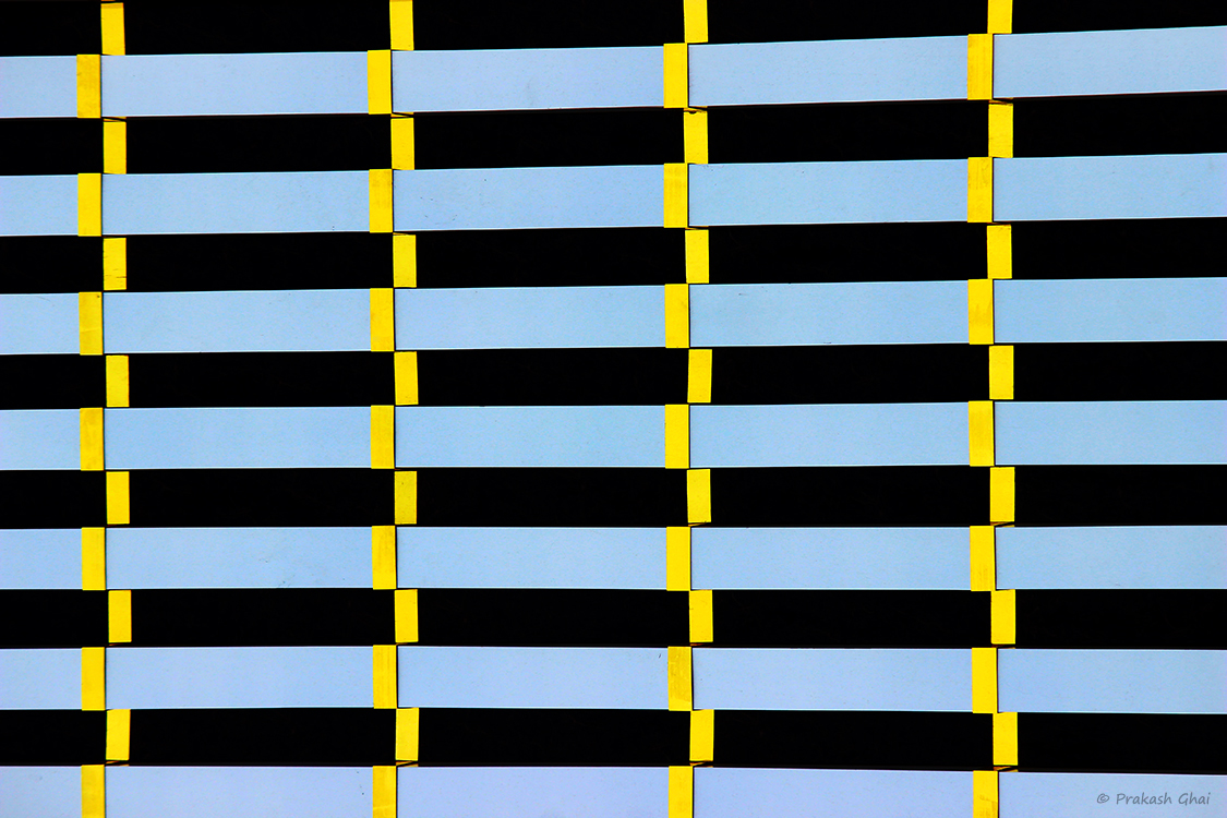 A Minimalist Photo of Horizontal blue lines in repetition being vertically crossed by the yellow ones.