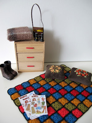 One-twelfth scale miniature 1940s chest of drawers, afghan rug, embroidered cushions, tramping boots, blanket and binoculars.