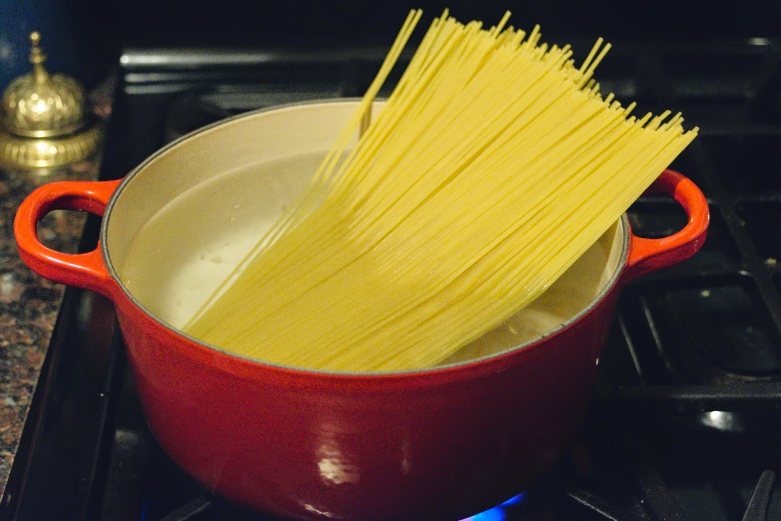 Pasta being added to the pot of water on the stove.