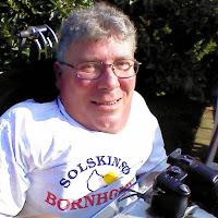 """Jan sidder i solen i sin kørestol med grønt i baggrunden. Han har gråt hår og briller og er i hvid t-shirt med teksten """"Borholm - solskinsø"""". I skødet har han et spejlreflekskamera."""