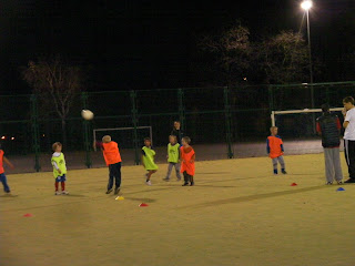 floodlit football with orange high visibility jackets