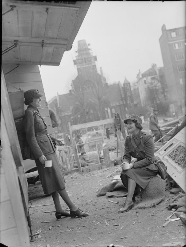 Women of WW2 MTC - Miss Winifred Ashford and Mrs Pat Macleod enjoy a cup of tea beside their mobile canteen amongst rubble and other debris. In the background, St. James's Church, Paddington, can be seen. The spire of the church is shrouded in scaffolding, as it was badly damaged in an air raid.