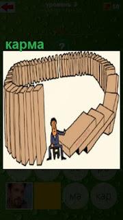 мужчина сидит на табуретке и вокруг забор, рукой роняет стены как домино