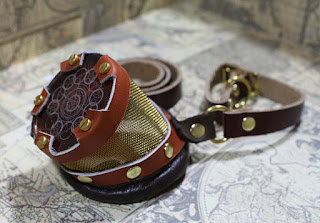 Steampunk brass mesh and leather monocle/monogoggle with red colored lens with image/diagram on it