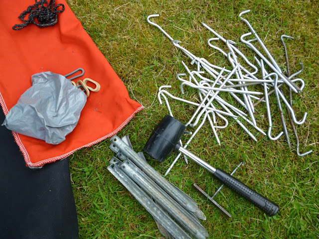 tent pegs and mallet on a lawn