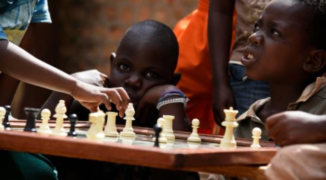 """Children practice a game of chess at the Som Chess Academy at Katwe, a Kampala suburb. By Isaac Kasamani (AFP) Kampala (AFP) - Standing on a drab side-street next to an open sewer in the Ugandan capital Kampala, Brian Mugabi points to the site of his former family home and reflects on how much the game of chess has changed their lives.  Ten years ago Mugabi lived in abject poverty in Katwe, a slum in Kampala where it's a constant struggle to get by. But at a makeshift chess club in the heart of the neighbourhood, his sister Phiona Mutesi suddenly displayed an extraordinary, raw talent for the game.  The family's story is now the basis for the feel-good Disney movie """"Queen of Katwe"""" which premiered in Uganda last weekend with Oscar-winning Kenyan actress Lupita Nyong'o playing the role of Phiona's mother."""