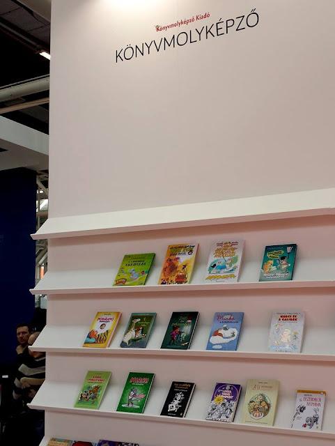Ecsédi Orsolya Cirrus a Tűzfalon című ifjúsági regénye a Bolognai Nemzetközi Gyerekkönyv- és Illusztrációs Vásáron, a Könyvmolyképző standján.