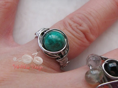 Twice Around the World (TAW) wire wrapped ring with Malachite around finger