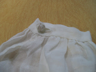 Thread button and hand-sewn buttonhole on repro 16th century smock.