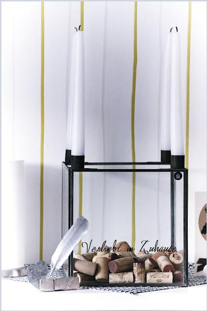 lackierte Feder als Dekoration vor Kerzenständer