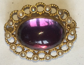 Purple cabochon gem with reflected window.