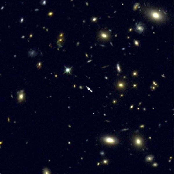 Thiên hà COSMOS-1908 nằm ở giữa hình (mũi tên trắng) cùng với những thiên hà khác ở gần Trái Đất hơn. Credit: Kính Viễn vọng Không gian Hubble.