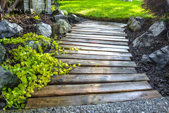 Learn how to build and upkeep this pretty pallet wood garden walkway path! Click for the instructions and how to upkeep! #palletwood #pallets #gardening #gardenpath