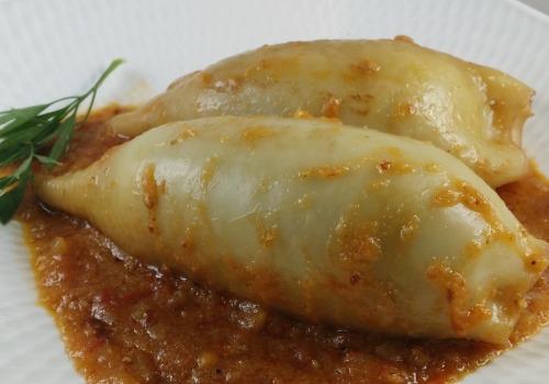 Un par de calamares en un plato con una salsa de tomate
