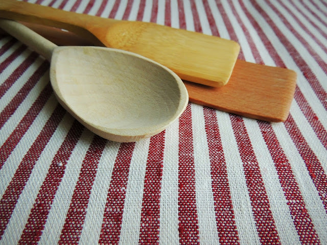 farmhouse wooden spoons spatulas on cutting board grainsack towel
