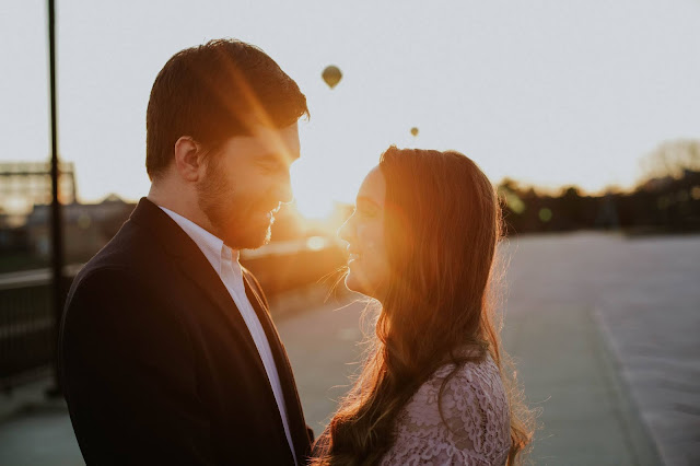 the sun is setting behind a couple on a bridge in indianapolis and the couple is positioned so the sun is in between them and there is a flare