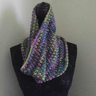 A multicolored cowl in bright spring colors on a black lace mannequin