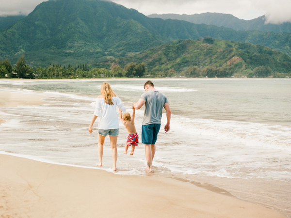 mom, dad & toddler plus the beautiful green mountains surrounding Hanalei Bay