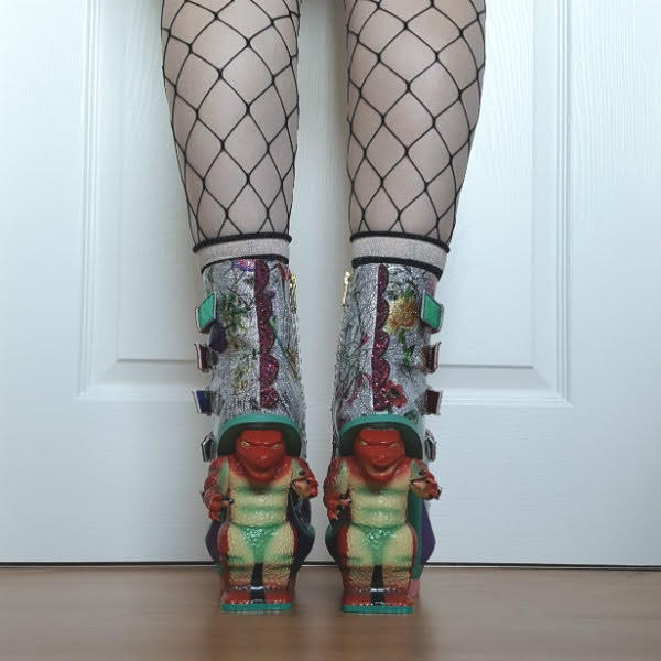 back view of dinosaur heels on feet with glitter spine and floral uppers