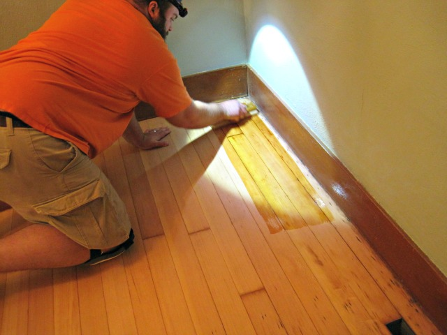 man applying varnish hardwood floor applicator