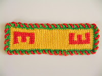 A rectangular piece of tricot simple stitch fabric. The yellow fabric has the red letter 'E' worked into it using a tricot intarsia method. The fabric is bordered with a green and red braided stitch. The square grid-like texture can be seen.