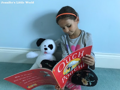 Child reading a book to her teddy bear