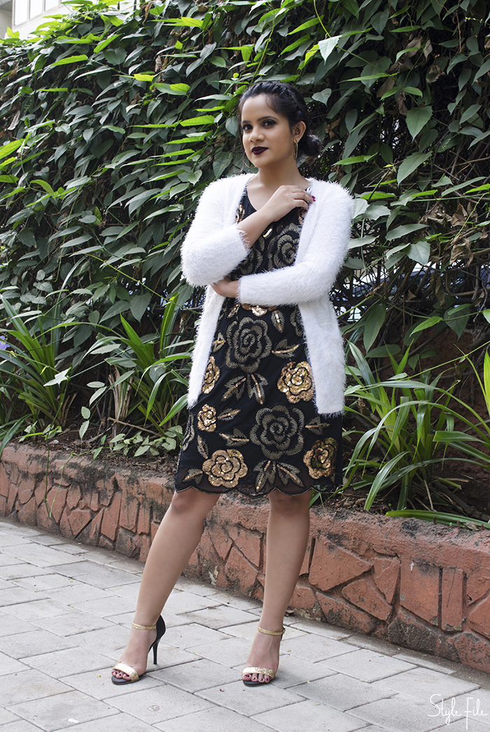 An image of a young woman wearing an outfit with a gold and black embroidered sequin dress with a white faux fur coat, gold glitter heels, braided side bun and dark lip