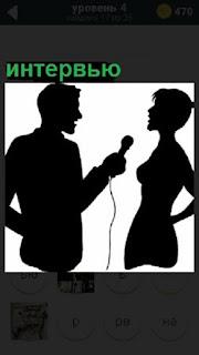 Мужчина журналист берет интервью у женщины, показаны силуэты