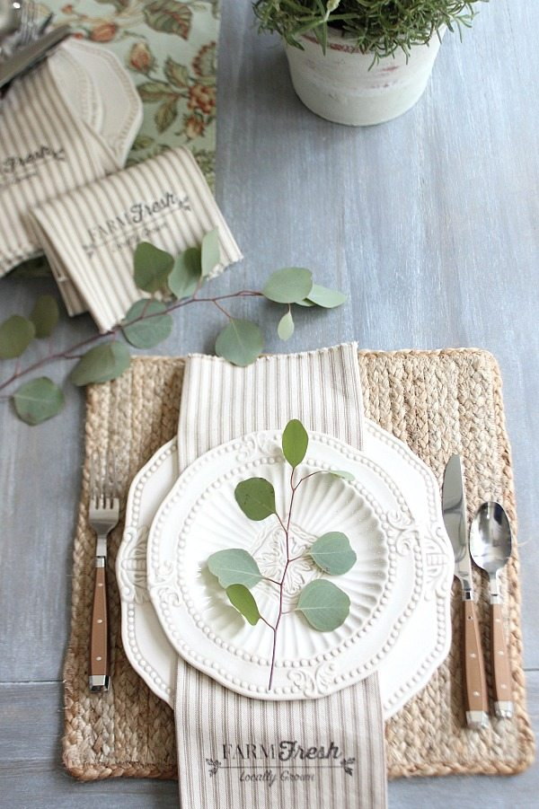 Beautiful place setting with jute placemat on a whitewashed table.