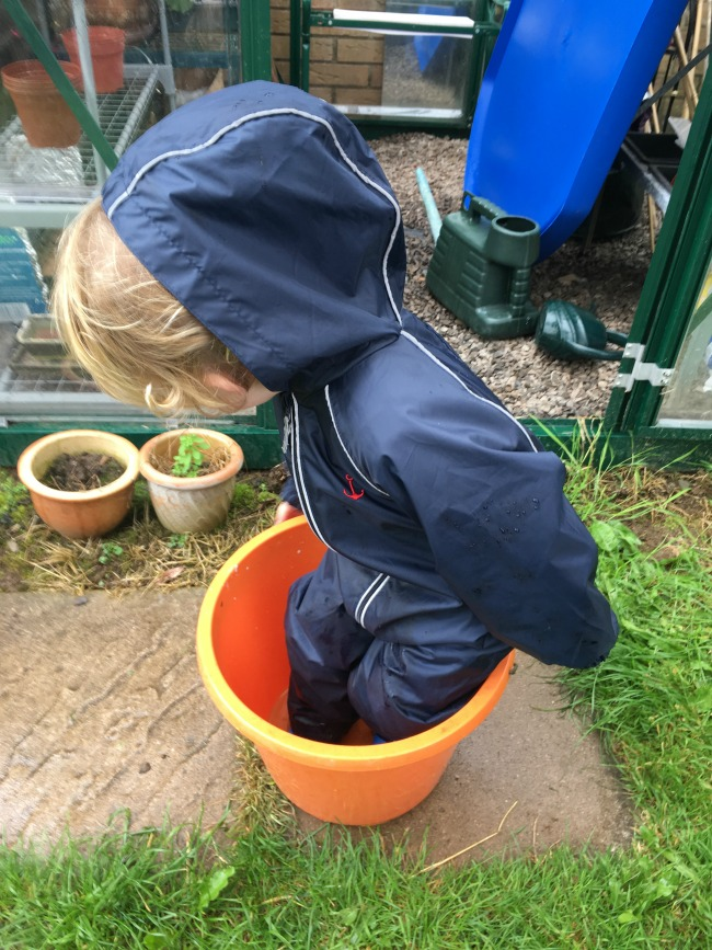 8-ways-to-entertain-a-toddler-in-a-typical-British-Summer-toddler-stood-in-bucket