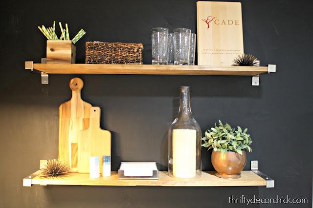 Wood shelves on black chalkboard wall